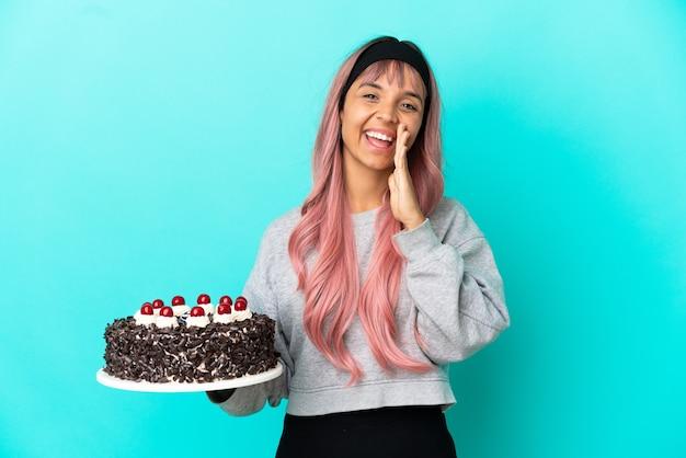 Молодая женщина с розовыми волосами держит праздничный торт на синем фоне и кричит с широко открытым ртом