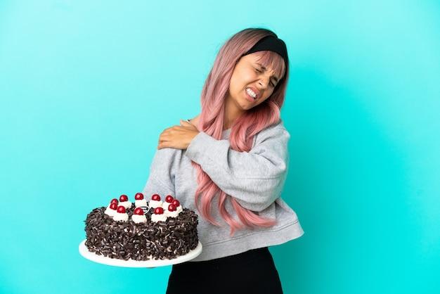 Молодая женщина с розовыми волосами, держащая праздничный торт на синем фоне, страдает от боли в плече из-за того, что приложила усилие
