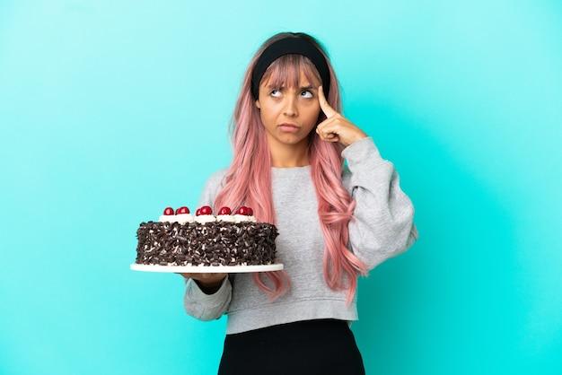 아이디어를 생각하는 파란색 배경에 고립 된 생일 케이크를 들고 분홍색 머리를 가진 젊은 여자