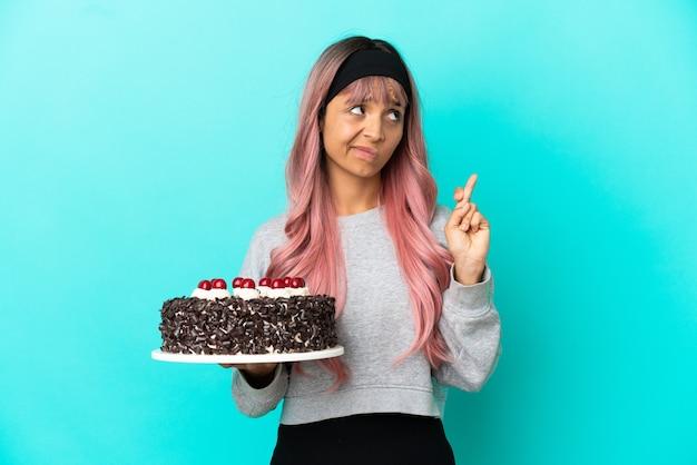 파란 배경에 격리된 생일 케이크를 들고 분홍색 머리를 한 젊은 여성이 손가락을 교차하고 최고를 기원합니다