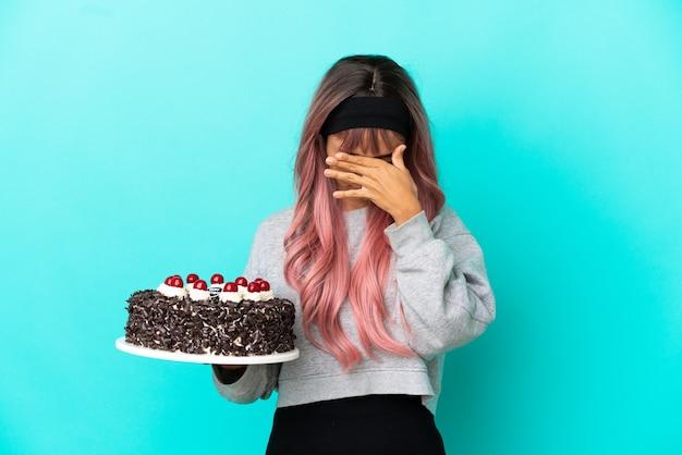 Молодая женщина с розовыми волосами держит праздничный торт на синем фоне с усталым и больным выражением лица