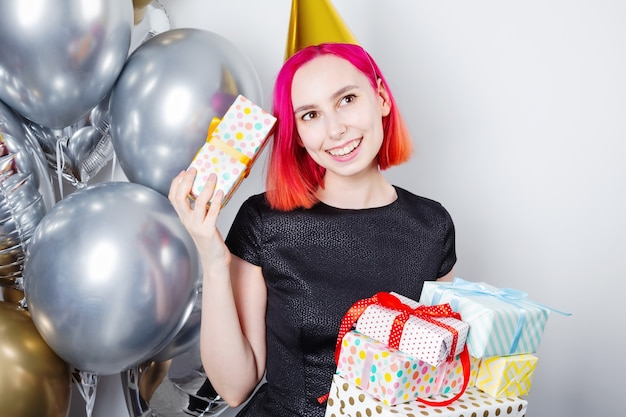Young woman with pink hair and party hat holds birthday gifts and smiles
