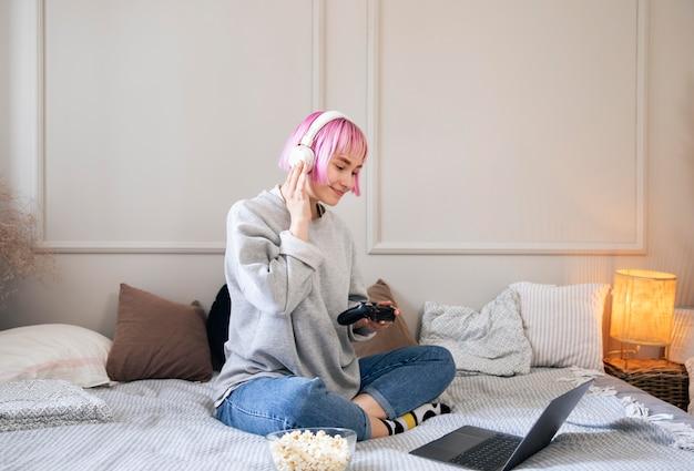 Молодая женщина с розовыми волосами играет в видеоигру