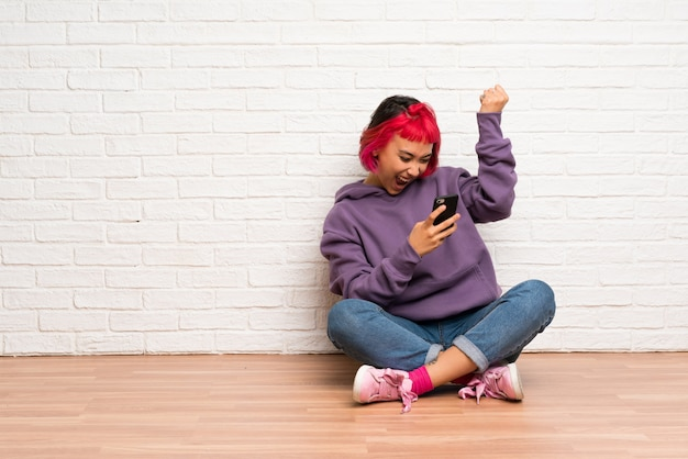 Young woman with pink hair sitting on the floor with phone in victory position