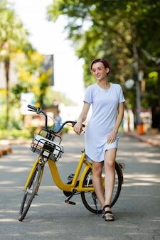 ピンクの髪の若い女性は夏にアイスクリームを食べる自転車で公園を散歩します。輸送の環境モード