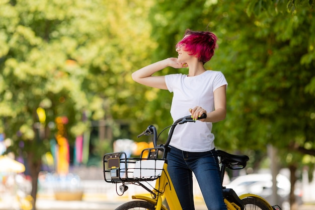 Young woman with pink hair walks in the park with a bike eating ice cream in the summer.