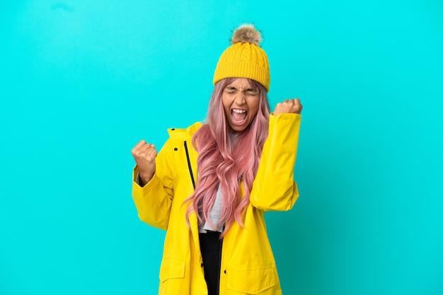 승리를 축하하는 파란색 배경에 격리된 방수 코트를 입고 분홍색 머리를 한 젊은 여성