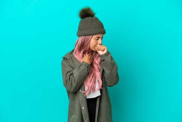 たくさん咳をする青い背景で隔離の防雨コートを着ているピンクの髪の若い女性