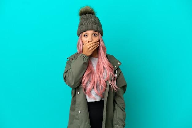 Молодая женщина с розовыми волосами, одетая в непромокаемое пальто на синем фоне, прикрывая рот рукой