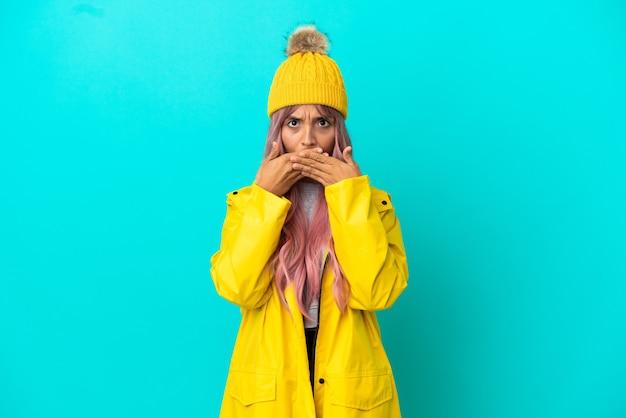 Молодая женщина с розовыми волосами в непромокаемом пальто на синем фоне, прикрывая рот руками