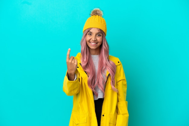 Молодая женщина с розовыми волосами в непромокаемом пальто на синем фоне делает приближающийся жест