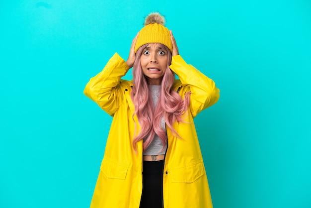 神経質なジェスチャーをしている青い背景で隔離の防雨コートを着ているピンクの髪の若い女性