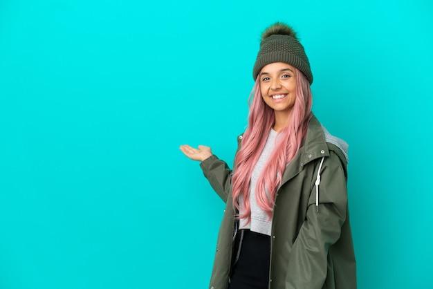 Молодая женщина с розовыми волосами в непромокаемом пальто на синем фоне протягивает руки в сторону, приглашая приехать