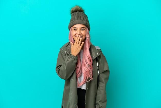 ピンクの髪の若い女性は、青い背景で隔離の防雨コートを着て幸せで笑顔の手で口を覆う