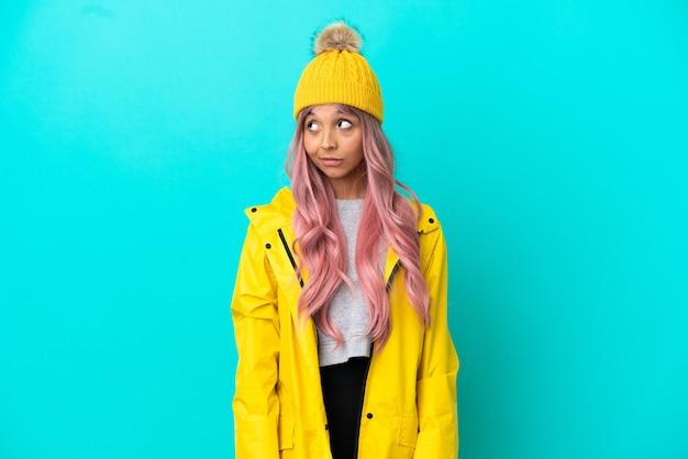파란색 배경에 격리된 방수 코트를 입고 분홍색 머리를 한 젊은 여성이 옆을 보면서 의심을 품고 있습니다.