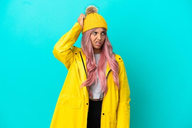 파란색 배경에 격리된 방수 코트를 입은 분홍색 머리를 한 젊은 여성이 머리를 긁는 동안 의심을 품고 있다