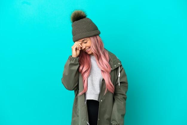 파란색 배경에 격리된 방수 코트를 입고 분홍색 머리를 한 젊은 여성이 웃고 있습니다.