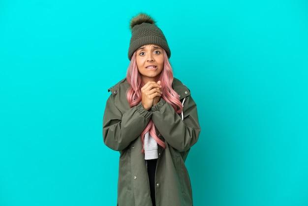 笑って青い背景で隔離の防雨コートを着ているピンクの髪の若い女性