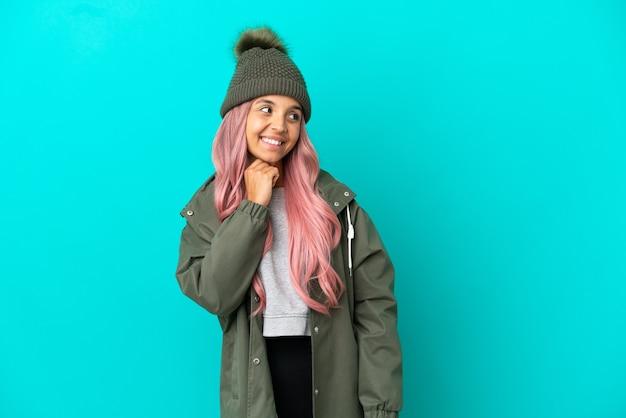 Молодая женщина с розовыми волосами в непромокаемом пальто на синем фоне смотрит вверх, улыбаясь