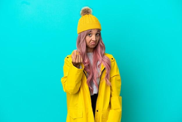 お金のジェスチャーを稼ぐ青い背景に分離された防雨コートを着ているピンクの髪の若い女性