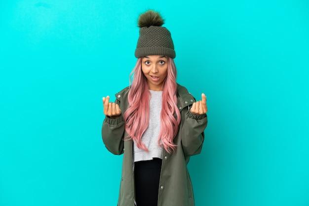 Молодая женщина с розовыми волосами в непромокаемом пальто на синем фоне делает денежный жест