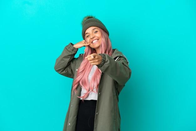 ピンクの髪の若い女性は、青い背景で隔離の防雨コートを着て電話ジェスチャーをし、正面を指しています