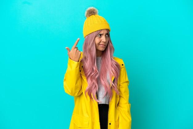 파란 배경에 격리된 방수 코트를 입은 분홍색 머리를 한 젊은 여성이 머리에 손가락을 대고 미친 듯한 제스처를 취한다
