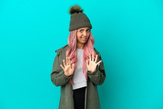 ピンクの髪の若い女性は、青い背景に分離された防雨コートを着て神経質な手を前に伸ばします
