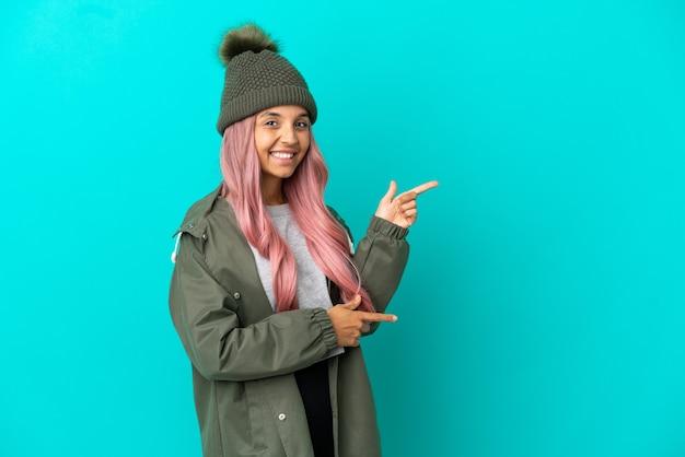 横に指を指している青い背景に分離された防雨コートを着ているピンクの髪の若い女性