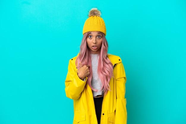 自分を指している青い背景で隔離の防雨コートを着ているピンクの髪の若い女性