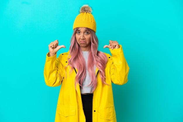 誇りと自己満足の青い背景に分離された防雨コートを着ているピンクの髪の若い女性