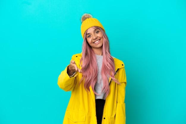 Молодая женщина с розовыми волосами, одетая в непромокаемое пальто на синем фоне, пожимая руку для заключения хорошей сделки
