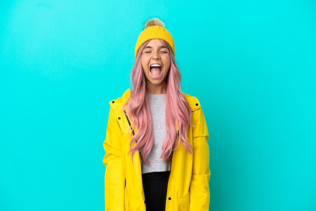 파란 배경에 격리된 방수 코트를 입은 분홍색 머리를 한 젊은 여성이 입을 크게 벌리고 앞으로 소리쳤다