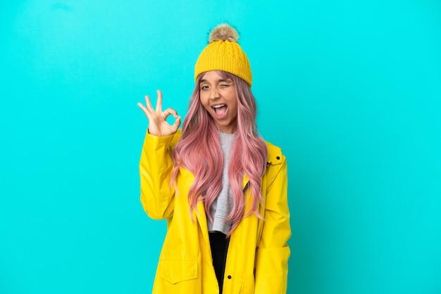 손가락으로 확인 표시를 보여주는 파란색 배경에 고립 된 방수 코트를 입고 분홍색 머리를 가진 젊은 여자