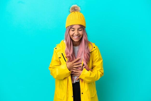 파란색 배경에 격리된 방수 코트를 입고 분홍색 머리를 한 젊은 여성이 많이 웃고 있습니다.
