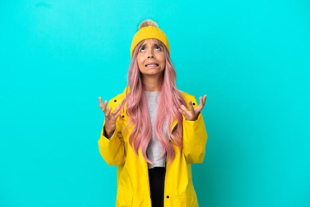 青い背景に分離された防雨コートを着ているピンクの髪の若い女性は圧倒されます