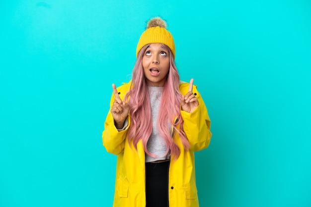 青い背景で隔離の防雨コートを着ているピンクの髪の若い女性は驚いて上向き