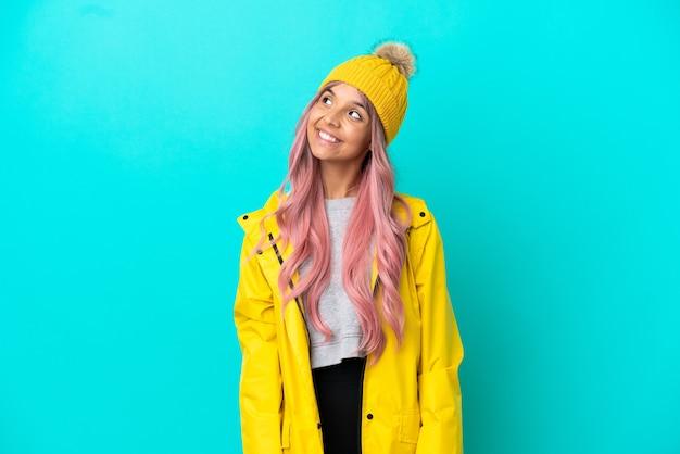 Молодая женщина с розовыми волосами в непромокаемом пальто на синем фоне думает об идее, глядя вверх