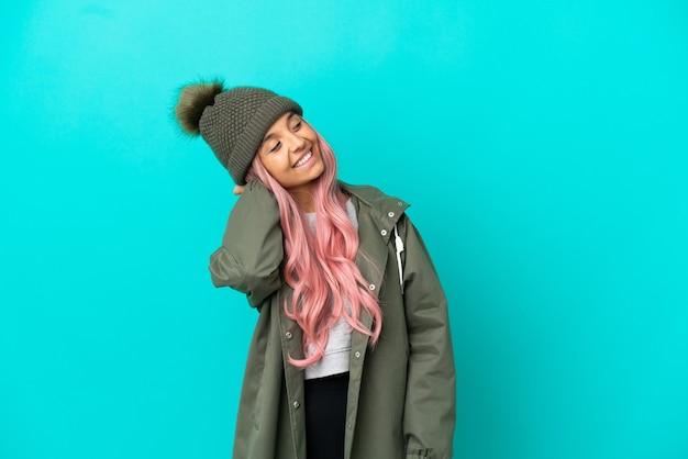 Молодая женщина с розовыми волосами в непромокаемом пальто на синем фоне думает об идее