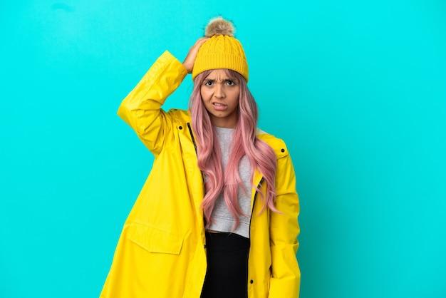 Молодая женщина с розовыми волосами в непромокаемом пальто изолирована на синем фоне с выражением разочарования и непонимания