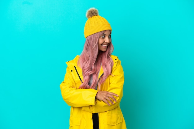 腕を組んで幸せな青い背景で隔離の防雨コートを着ているピンクの髪の若い女性