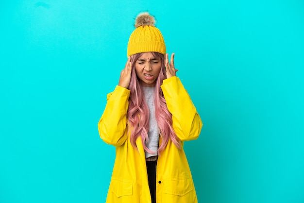 두통과 함께 파란색 배경에 고립 된 방수 코트를 입고 분홍색 머리를 가진 젊은 여자