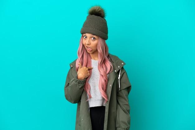 Молодая женщина с розовыми волосами в непромокаемом пальто на синем фоне с удивленным выражением лица