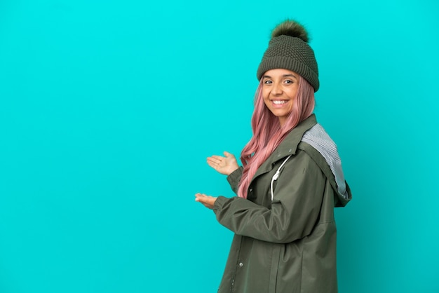 Young woman with pink hair wearing a rainproof coat isolated on blue background extending hands to the side for inviting to come
