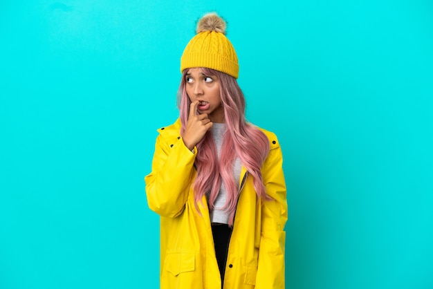 Young woman with pink hair wearing a rainproof coat isolated on blue background nervous and scared
