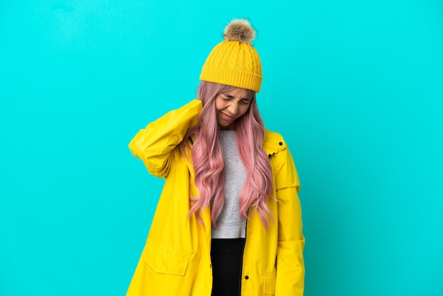Young woman with pink hair wearing a rainproof coat isolated on blue background with neckache