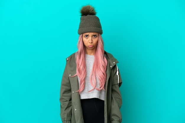 Young woman with pink hair wearing a rainproof coat isolated on blue background with sad expression