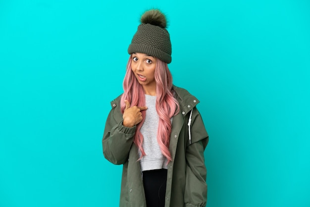 Young woman with pink hair wearing a rainproof coat isolated on blue background with surprise facial expression