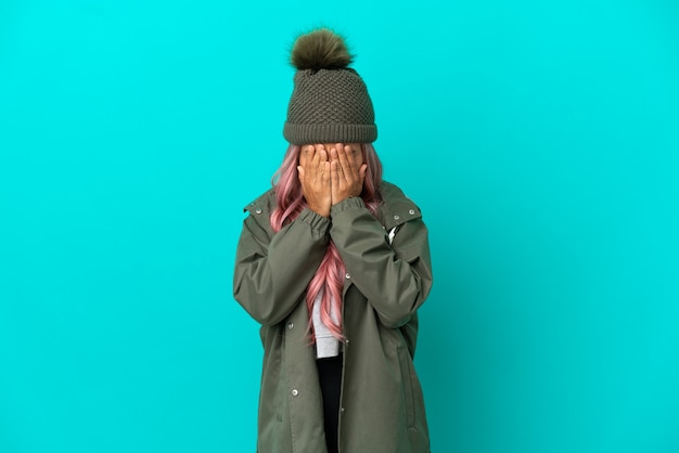 Young woman with pink hair wearing a rainproof coat isolated on blue background with tired and sick expression