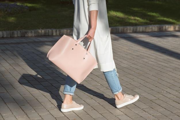通りを歩きながらピンクのハンドバッグを持つ若い女性